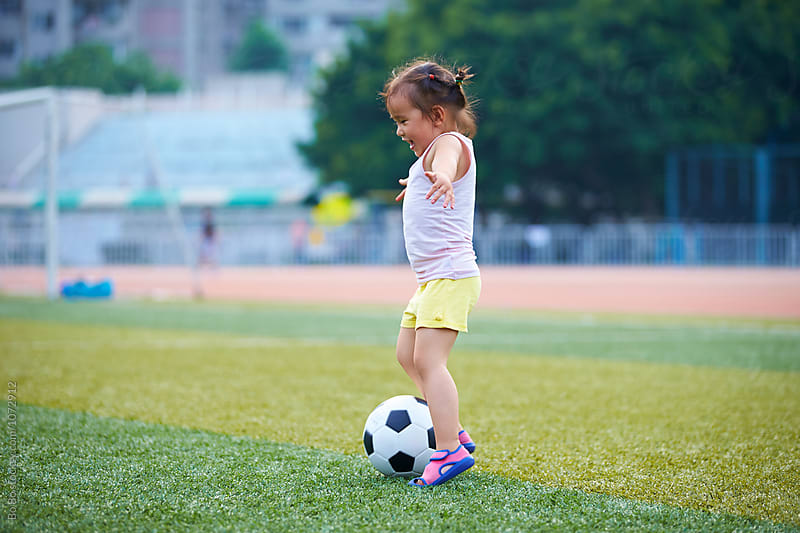 little asian or Chinese girl playing football outdoor in the football field by Bo Bo for Stocksy United