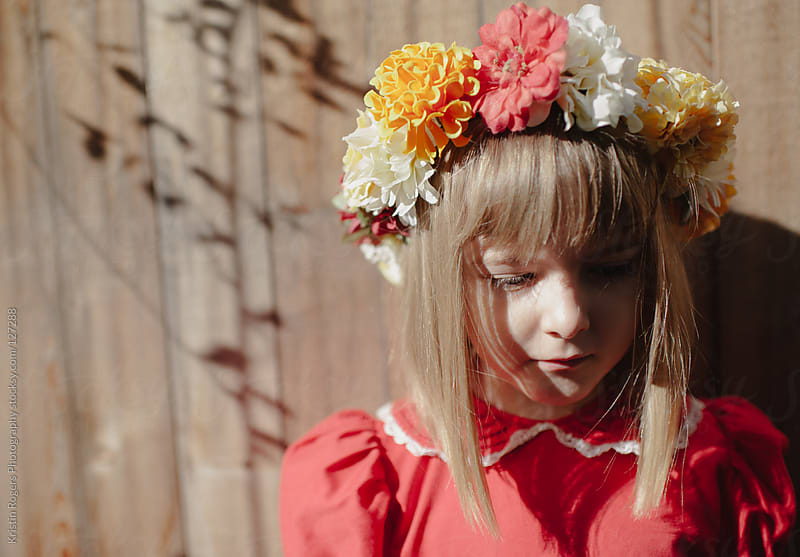 Young girl in red dress wearing a homemade floral crown  by Kristin Rogers Photography for Stocksy United