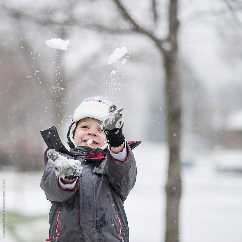 Boy throwing new snow up in the air by Cameron Whitman for Stocksy United