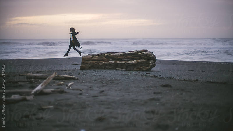 woman on beach log by Sam Hurd Photography for Stocksy United