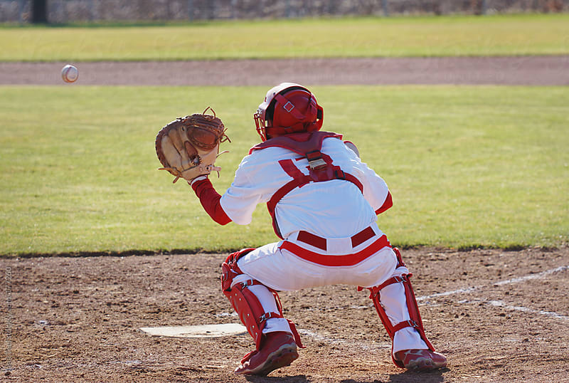 A catcher prepares to catch a baseball pitched to him by Tana Teel for Stocksy United