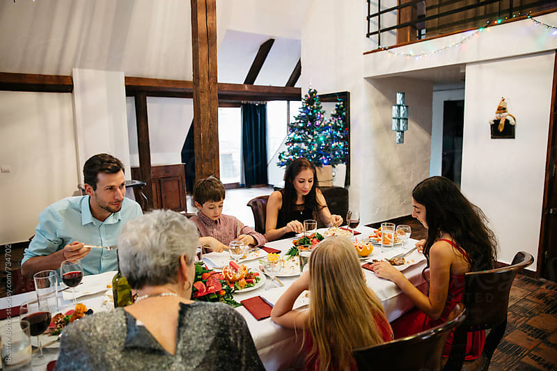 Family eating Christmas dinner together at the table  by Beatrix Boros for Stocksy United