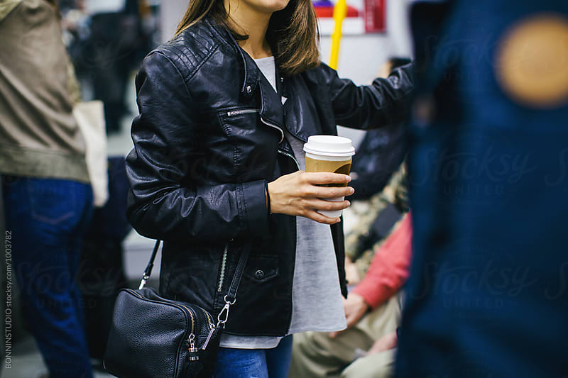 Closeup of tourist holding a coffee traveling in subway. by BONNINSTUDIO for Stocksy United