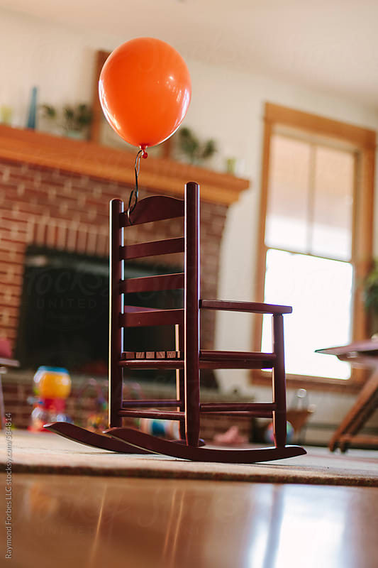 Someone attached an Orange Balloon to my Rocking Chair by Raymond Forbes LLC for Stocksy United
