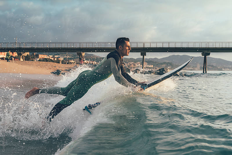 surfer getting into the sea by Guille Faingold for Stocksy United