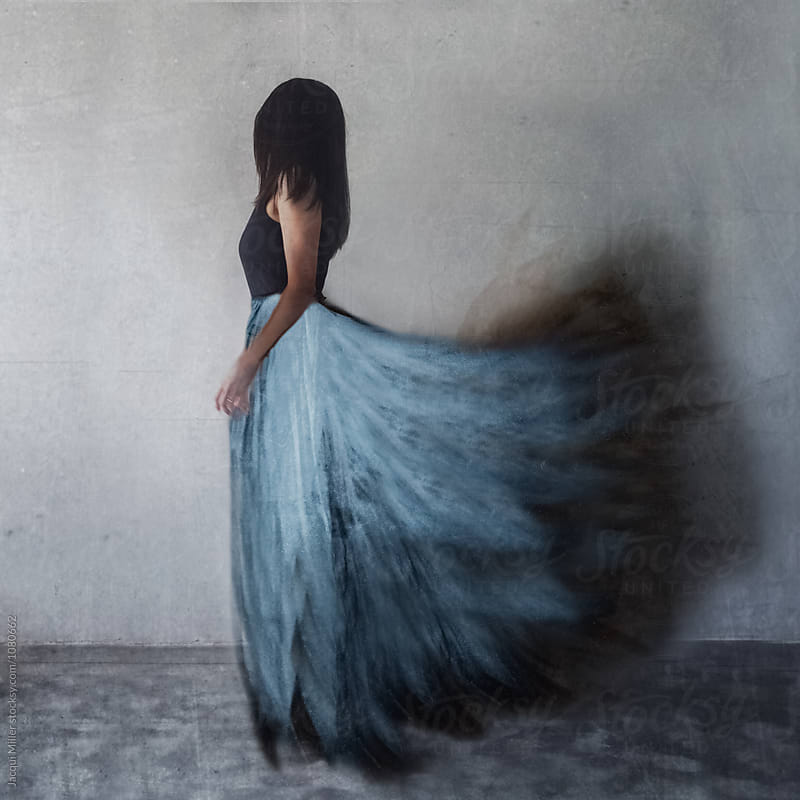 Woman with blue feather skirt - creative cell photography by Jacqui Miller for Stocksy United