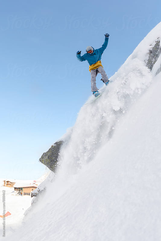 Man with snowboard jumping over the rocks  by RG&B Images for Stocksy United