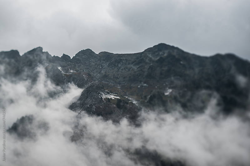 storm clouds on the top of mountain  by Javier Pardina for Stocksy United