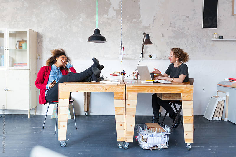 Two young women in a team working together in a hip workspace by Ivo de Bruijn for Stocksy United