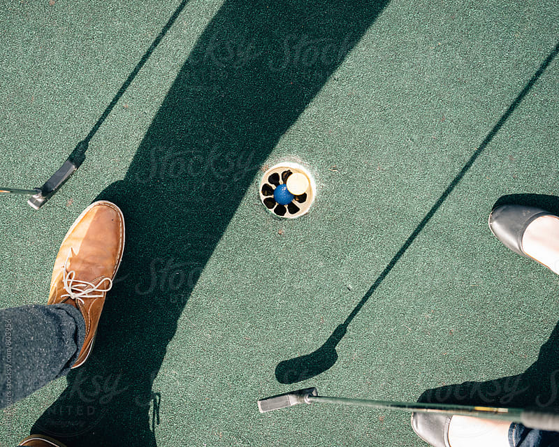 Feet and Clubs around Putt Putt Hole by Austin Rogers for Stocksy United