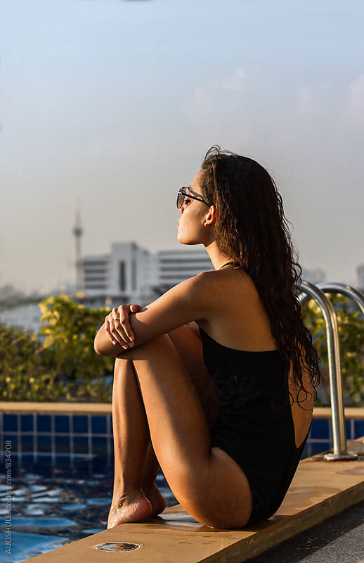 Beautiful young woman in swimsuit sitting by the pool on sunny day with city in background. by Marko Milanovic for Stocksy United