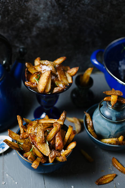 Homemade french fries in bowls on a table. by Darren Muir for Stocksy United