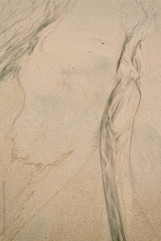 Patterns and textures in wet sand formed by receding tide by Marilar Irastorza for Stocksy United