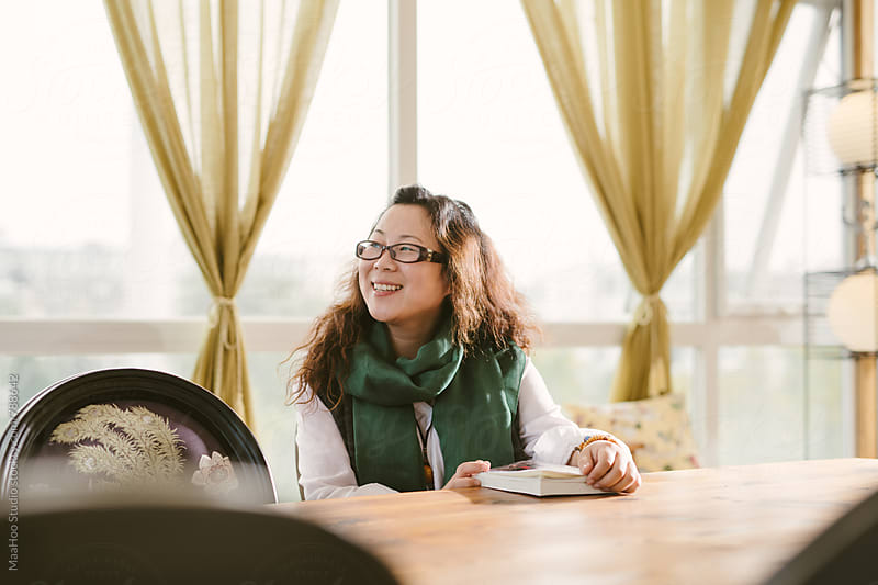 Young Chinese woman reading in cafe by MaaHoo Studio for Stocksy United