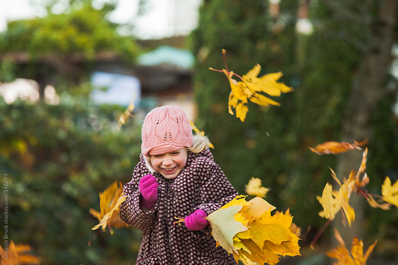 Autumn leaves fall on little girl's head. by Cherish Bryck for Stocksy United