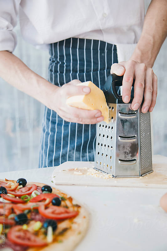 Pizza chef grates cheese by Danil Nevsky for Stocksy United