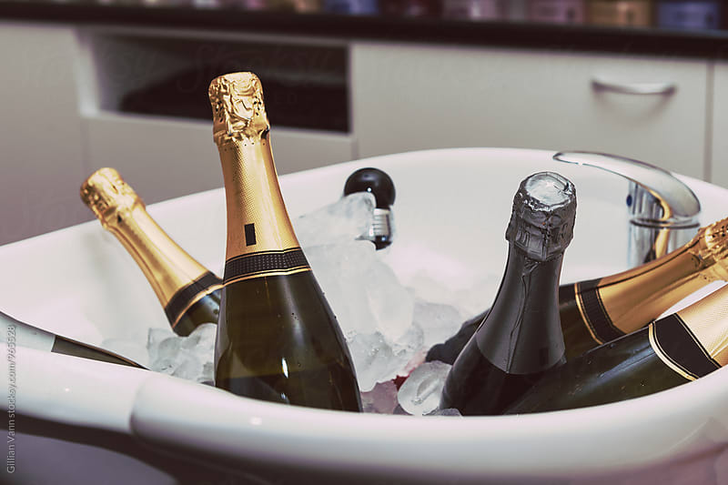 champagne wine chilling in a sink filled with ice by Gillian Vann for Stocksy United