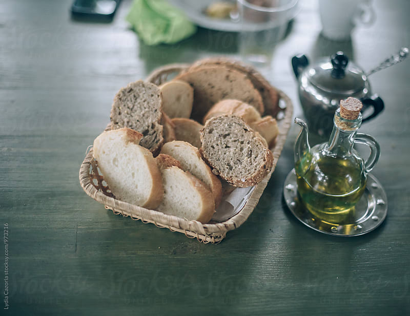 Home-baked bread on a basket of bread on the table by Lydia Cazorla for Stocksy United