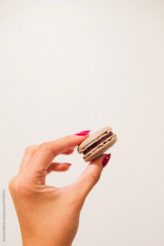 Female hand holding macaroon by Jovana Rikalo for Stocksy United