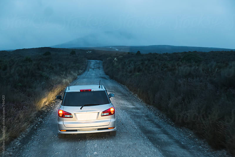 Car driving to hiking trail on remote dirt road in early morning by Matthew Spaulding for Stocksy United