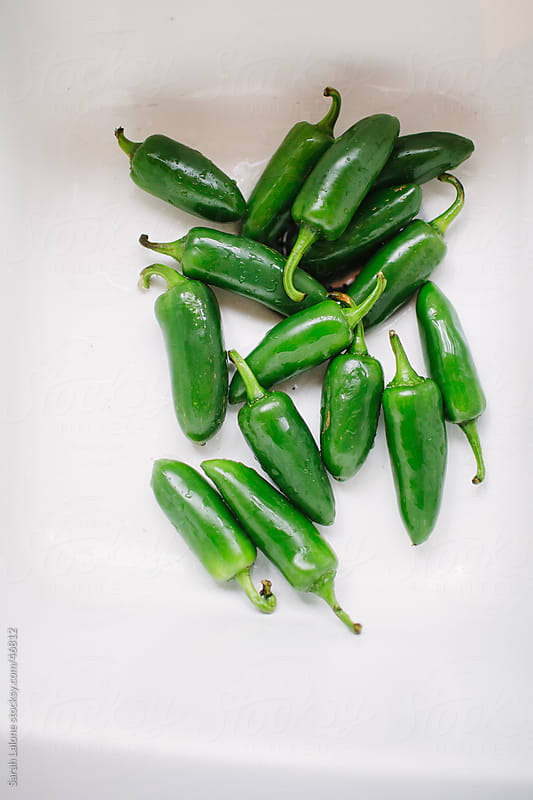 Wet jalapeno peppers in a white sink. by Sarah Lalone for Stocksy United