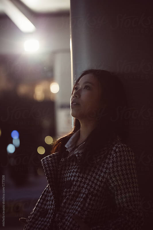 Portrait of young asian woman outdoors by night by michela ravasio for Stocksy United