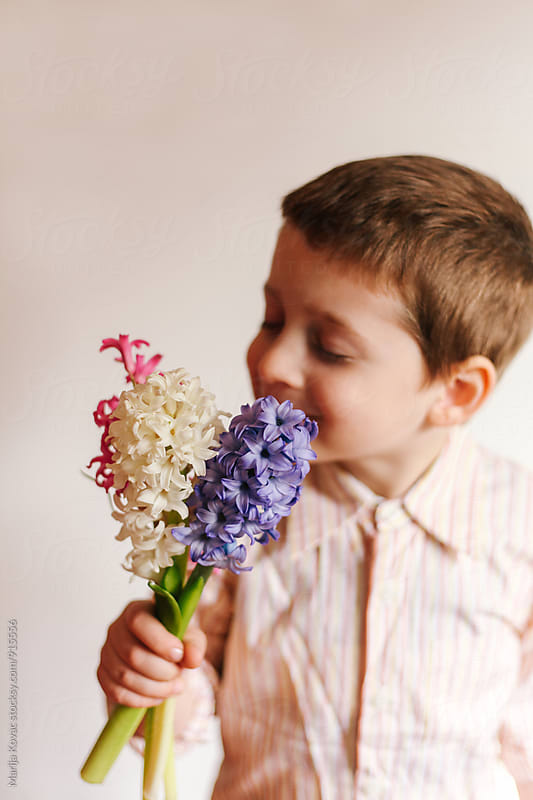 Male child holding a bouquet of flowers by Marija Kovac for Stocksy United