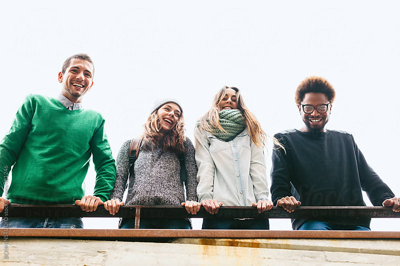 Smiling group of friends hanging out outdoors. by BONNINSTUDIO for Stocksy United