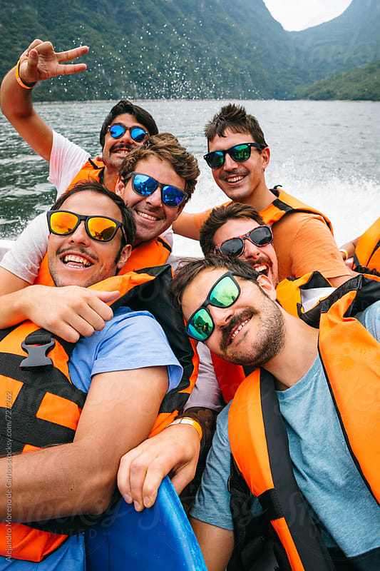 Group of six friends with life jackets and sunglasses having fun on a speedboat in a lake by Alejandro Moreno de Carlos for Stocksy United