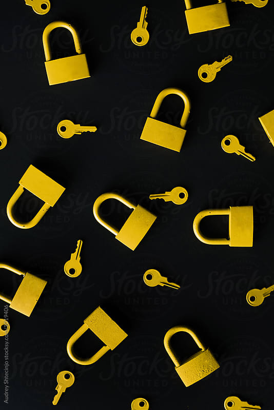 Yellow keys and locks on black background by Marko Milanovic for Stocksy United
