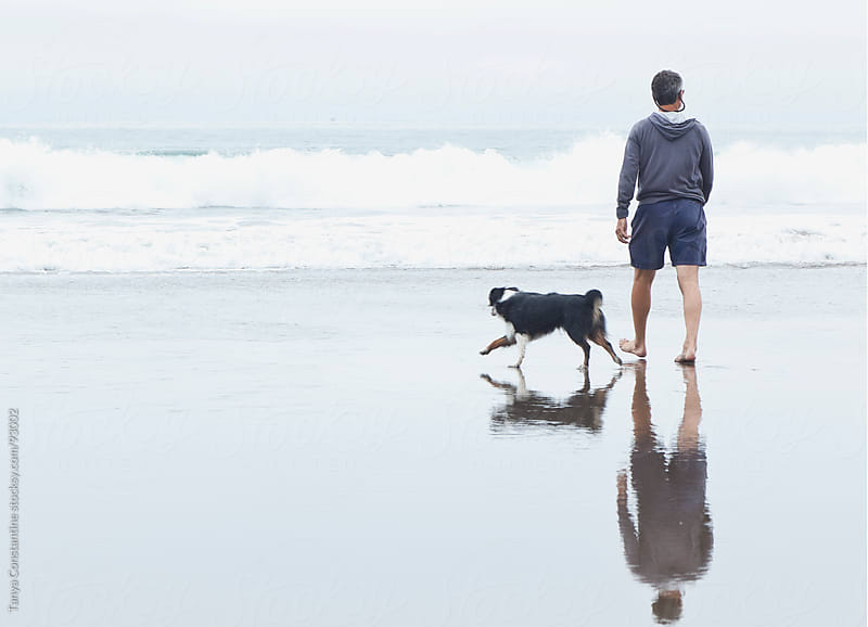 man walking his dog at the beach by Tanya Constantine for Stocksy United