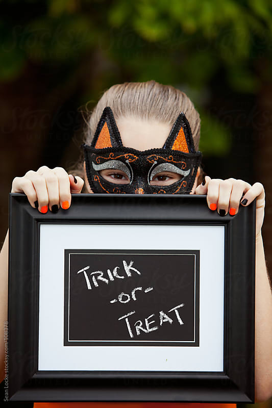 Halloween: Cat Girl Child Holding Halloween Message by Sean Locke for Stocksy United