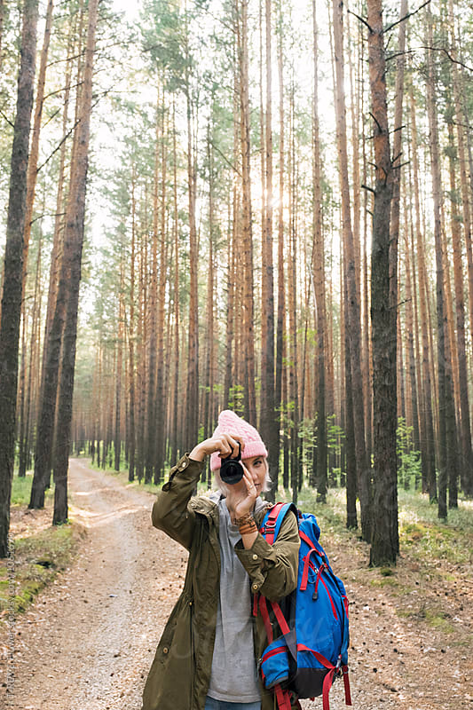 Girl in pink hat taking photo with camera in forest by Danil Nevsky for Stocksy United