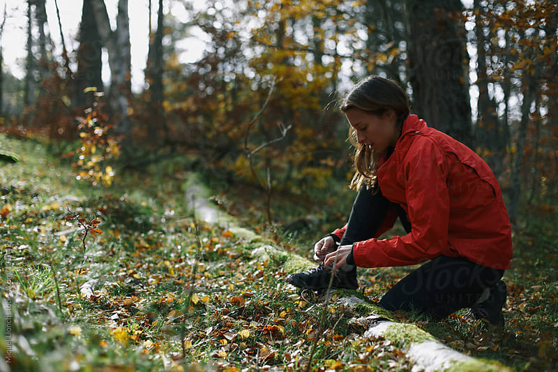 Woman runner tying her shoe outdoor in the forest by Miquel Llonch for Stocksy United