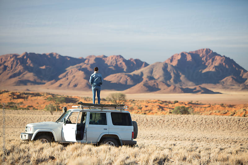 Woman on a roadtrip in scenic desert landscape by Micky Wiswedel for Stocksy United