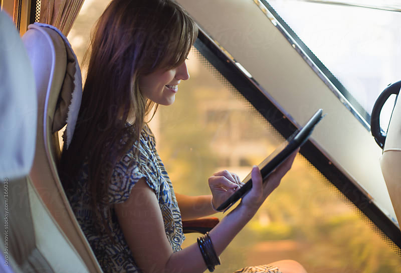 Young woman reading an e-book in the bus by Jovo Jovanovic for Stocksy United