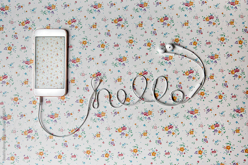 Hello written with a cellphone cable on a floral pattern background by Beatrix Boros for Stocksy United
