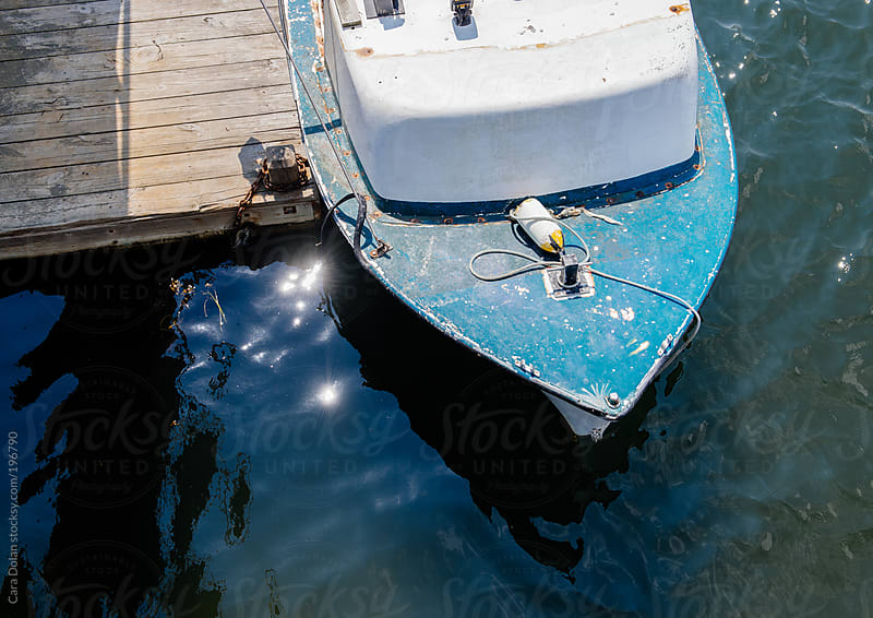Overhead view of a boat tied to a dock by Cara Dolan for Stocksy United