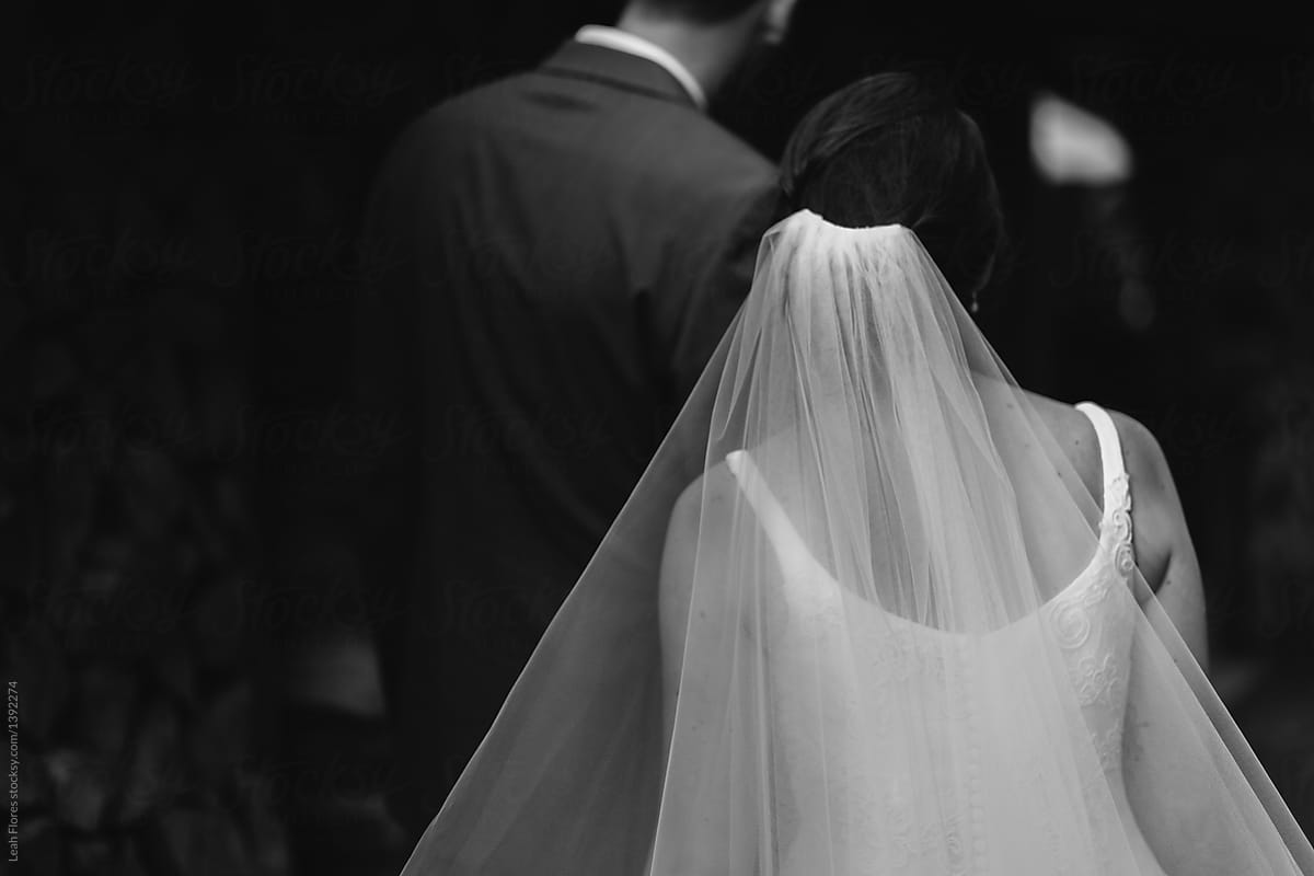Romantic black and white photograph of wedding couple with sweeping veil by leah flores for stocksy