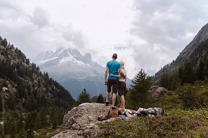 Young couple embracing and taking in the mountain view by Neil Warburton for Stocksy United