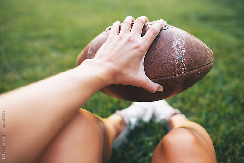 woman's hand holding a football in the backyard  by Kelly Knox for Stocksy United