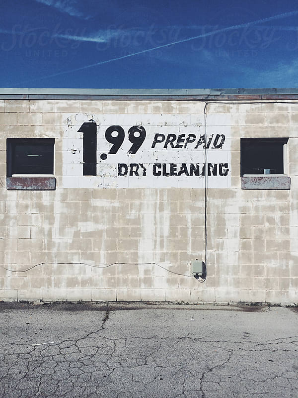Sign on a wall for prepaid dry cleaning for 1.99 by Justin March for Stocksy United