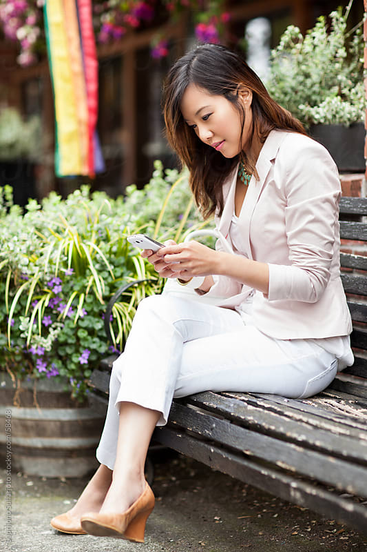 Beautiful Asian woman texting on her phone by Suprijono Suharjoto for Stocksy United