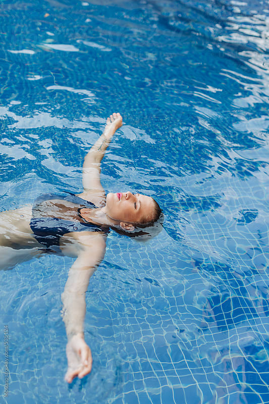Woman Floating in the Pool by Mosuno for Stocksy United