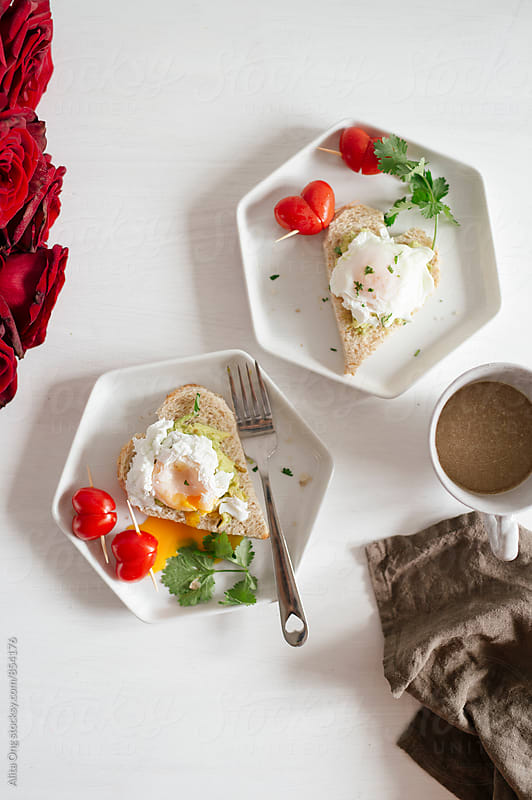 Heart-shaped avocado toast with poached egg and cherry tomatoes by Alita Ong for Stocksy United