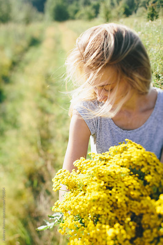 Young woman holding big bouquet of yellow wildflowers by Andrey Pavlov for Stocksy United