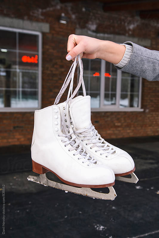 Close-up of woman's hand holding white skates by Danil Nevsky for Stocksy United