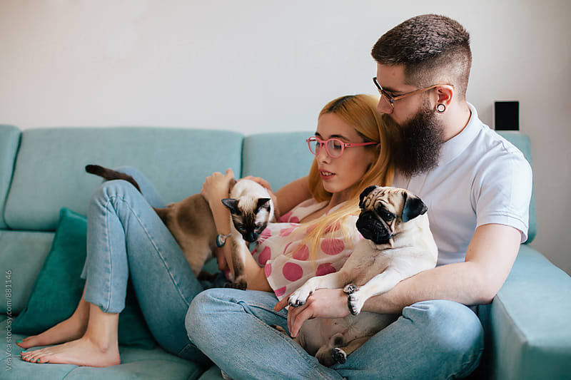 Young couple sitting on a couch with their pets  by Marija Mandic for Stocksy United