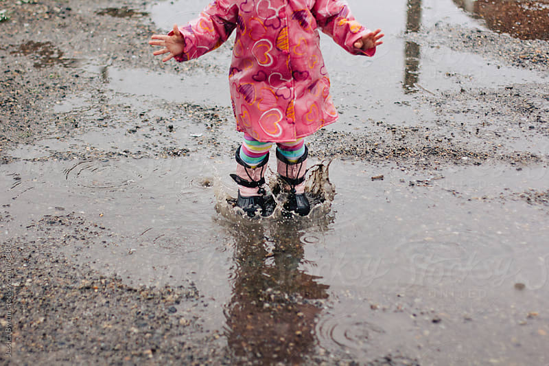 Toddler girl in a pink raincoat jumping in big mud puddles. by Jessica Byrum for Stocksy United
