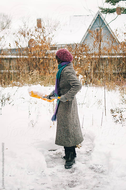 girl shoveling snow from her driveway by Deirdre Malfatto for Stocksy United